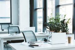 Headsets and laptops on tables. In modern office stock photography