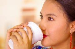 Headshot ładna młoda kobieta jest ubranym tradycyjną andyjską bluzkę, pije kawę od białego kubka Obrazy Stock