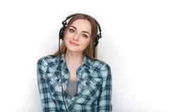 Headshot μιας νέας λατρευτής ξανθής γυναίκας στο μπλε πουκάμισο καρό που ακούει τα μεγάλα επαγγελματικά ακουστικά του DJ Στοκ Εικόνες