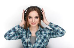 Headshot μιας νέας λατρευτής ξανθής γυναίκας στο μπλε πουκάμισο καρό που ακούει τα μεγάλα επαγγελματικά ακουστικά του DJ Στοκ φωτογραφίες με δικαίωμα ελεύθερης χρήσης