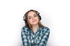 Headshot μιας νέας λατρευτής ξανθής γυναίκας στο μπλε πουκάμισο καρό που ακούει τα μεγάλα επαγγελματικά ακουστικά του DJ Στοκ Εικόνα