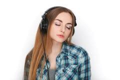 Headshot μιας νέας λατρευτής ξανθής γυναίκας στο μπλε πουκάμισο καρό που ακούει τα μεγάλα επαγγελματικά ακουστικά του DJ Στοκ Φωτογραφία