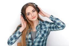 Headshot μιας νέας λατρευτής ξανθής γυναίκας στο μπλε πουκάμισο καρό που ακούει τα μεγάλα επαγγελματικά ακουστικά του DJ Στοκ Φωτογραφίες