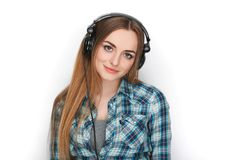 Headshot μιας νέας λατρευτής ξανθής γυναίκας στο μπλε πουκάμισο καρό που ακούει τα μεγάλα επαγγελματικά ακουστικά του DJ Στοκ εικόνα με δικαίωμα ελεύθερης χρήσης