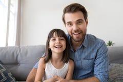 Headshot της ευτυχούς κόρης και του φιλικού πατέρα που μιλούν στο webcam στοκ φωτογραφία