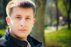 Headshot молодого человека ся на камере в парке Стоковые Фотографии RF