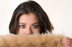 Headshot aantrekkelijke donkerbruine onder ogen ziende camera die de helft behandelen haar gezichts met bruine bontkleding, witte Stock Afbeelding