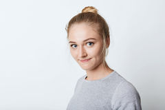 Headshot of adorable blue-eyed female with light hait tied in knot, looking with delightful expression into camera, going to have. Walk. Female teenager resting Stock Photo