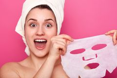 Headshot of amazed beautiful young woman holds cosmetic mask, feels refreshed and energized, has wrapped towel on head, looks with royalty free stock photography
