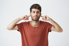 Headshot of annoyed stylish italian guy in red t shirt looking grumpy, closing ears with fingers showing disrespect on. His friend words Royalty Free Stock Photos