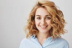 Headshot atrakcyjny żeński coworker w błękitnej bluzce z krótkiej blondynki kędzierzawym włosy, ono uśmiecha się z ufnym i życzli fotografia stock