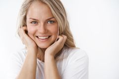 Headshot of attractive adult blond woman with tattoo leaning face on palms and smiling lovely making romantic gazes at. Camera feeling soft and silk skin royalty free stock photos