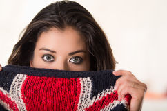 Headshot attractive brunette facing camera covering half her face with british flag patterned clothing, white studio. Background Stock Images