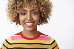 Headshot of attractive tender and friendly-looking outgoing joyful young dark-skinned woman with fair curly haircut in. Striped sweater smiling delighted and stock image