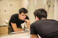 Headshot of attractive young man brushing teeth Stock Images