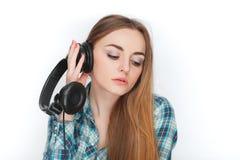 Headshot av en ung förtjusande blond kvinna i blå plädskjorta som tycker om lyssnande musik till stor professionelldj-hörlurar Arkivbilder