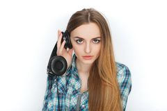 Headshot av en ung förtjusande blond kvinna i blå plädskjorta som tycker om lyssnande musik till stor professionelldj-hörlurar Arkivfoton