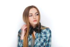 Headshot av en ung förtjusande blond kvinna i blå plädskjorta som tycker om lyssnande musik till stor professionelldj-hörlurar Royaltyfri Foto