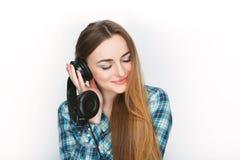Headshot av en ung förtjusande blond kvinna i blå plädskjorta som tycker om lyssnande musik till stor professionelldj-hörlurar Arkivbild