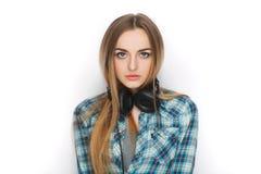 Headshot av en ung förtjusande blond kvinna i blå plädskjorta som tycker om lyssnande musik till stor professionelldj-hörlurar Fotografering för Bildbyråer