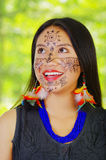 Headshot beautiful amazonian exotic woman with facial paint and black dress, posing happilyfor camera, forest background Stock Photo