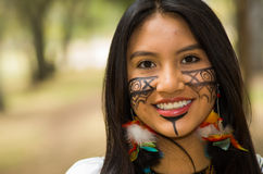 Headshot beautiful Amazonian woman, indigenous facial paint and earrings with colorful feathers, posing happily for Royalty Free Stock Image