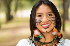 Headshot beautiful Amazonian woman, indigenous facial paint and earrings with colorful feathers, posing happily for Stock Image