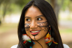 Headshot beautiful Amazonian woman, indigenous facial paint and earrings with colorful feathers, posing happily for Stock Photography