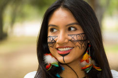 Headshot beautiful Amazonian woman, indigenous facial paint and earrings with colorful feathers, posing happily for Stock Photo