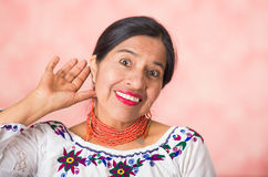 Headshot beautiful hispanic mother wearing traditional andean clothing, interacting holding hand behind ear while Stock Images