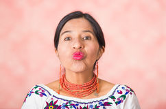 Headshot beautiful hispanic mother wearing traditional andean clothing, making kissing lips to camera, pink studio Royalty Free Stock Photos