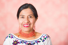 Headshot beautiful hispanic mother wearing traditional andean clothing, posing happily while smiling to camera, pink Stock Photo