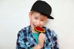 Headshot of beautiful little boy holding and biting lollipop looking at the camera with happy and joyful expression. Handsome boy Stock Photo