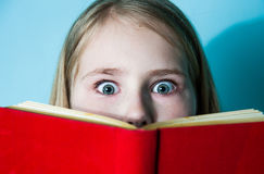Headshot beautiful little girl hiding behind book, looking scared. Face, facial expressions, emotions, reaction Stock Photography