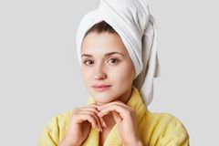 Headshot of beautiful lovely young female has cared healthy skin, wears towel on head, dressed in yellow bathrobe, looks directly stock photography
