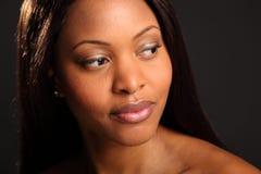 Headshot of beautiful serene black woman. Landscape style headshot of gorgeous, beautiful black woman, glancing away looking serene and peaceful Royalty Free Stock Photography