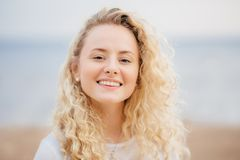 Headshot of beautiful woman with friendly smile, has healthy skin, being in good mood after unforgettable rest in resort country w royalty free stock image