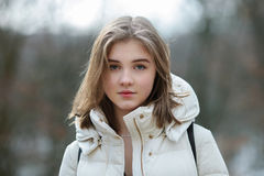 Headshot of beautiful young natural looking blonde woman posing on the spring city park in warm clothes. Positive emotions lifesty. Le concept stock image