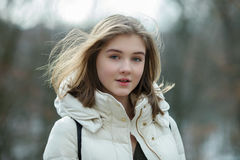 Headshot of beautiful young natural looking blonde woman posing on the spring city park in warm clothes. Positive emotions lifesty Stock Image