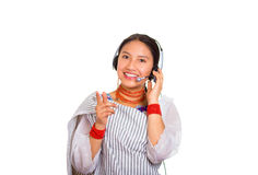 Headshot beautiful young woman wearing traditional andean shawl, red necklace and headset, interacting posing for camera Royalty Free Stock Photo