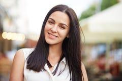 Headshot brunetki kobieta ono uśmiecha się joyfully, zdrową skórę, pozy przeciw zamazanemu tłu, cieszy się przespacerowanie z jej Fotografia Stock