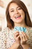 Headshot brunetki powabna kobieta trzyma up małych listy literuje słowo i ono uśmiecha się kamera mówi Zdjęcia Stock