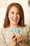 Headshot brunetki powabna kobieta trzyma up małych listy literuje słowo i ono uśmiecha się kamera mówi Obrazy Stock