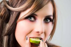 Headshot brunette, dark mystique look and green lipstick, biting on slice of lime while looking into camera Royalty Free Stock Photos