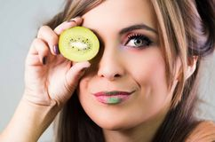 Headshot brunette, dark mystique look and green lipstick, covering one eye with open kiwi, looking into camera Stock Photos