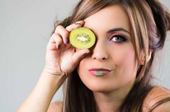 Headshot brunette, dark mystique look and green lipstick, covering one eye with open kiwi, looking into camera Royalty Free Stock Image