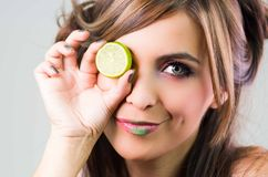 Headshot brunette, dark mystique look and green lipstick, covering one eye with open lime, looking into camera Royalty Free Stock Images