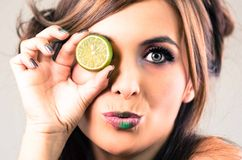 Headshot brunette, dark mystique look and green lipstick, covering one eye with open lime, looking into camera Stock Image