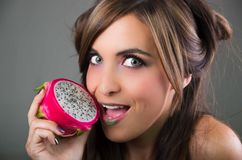 Headshot brunette, dark mystique look and green lipstick, holding open pink pitaya fruit next to mouth while sticking Stock Images