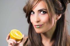 Headshot brunette with dark mystique look and green lipstick holding up an orange, grey background Stock Photo